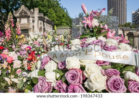 "Flowers on a grave with French words ""To my wife"" - stock photo"
