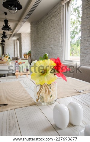 Flowers , salt and pepper on wood table in vintage style restaurant - stock photo