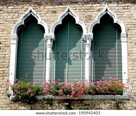 flowery balcony in Venetian style with arched windows of a historic residence in Venice - stock photo