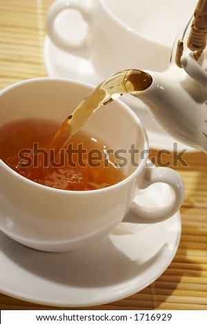 flowing golden tea into cup - stock photo
