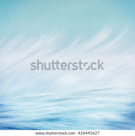 Flowing ocean water with motion blur and wispy clouds create a surrealistic seascape.  - stock photo