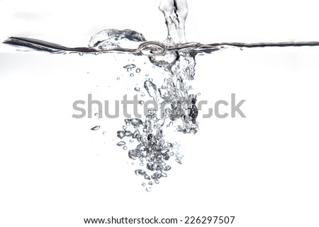 Flowing water and air bubbles over white background - stock photo