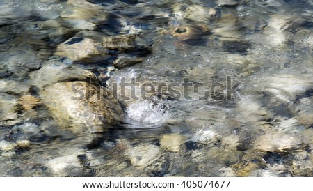 flowing water around rocks in a strem - stock photo