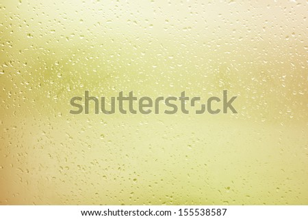 Flowing water drops on the glass in a gloomy autumn day - stock photo