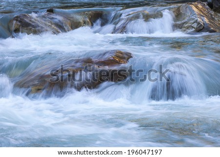 Flowing water in a rapid river - stock photo