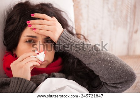 Flu. Closeup image of frustrated sick woman with red nose lying in bed in thick scarf holding tissue by her nose and touching her head - stock photo