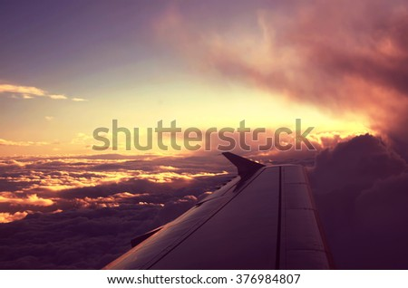 Fluffy clouds from the top and dramatic sunset, airplane view - stock photo