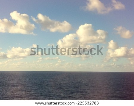 Fluffy clouds in the sky above a calm stretch of ocean. - stock photo