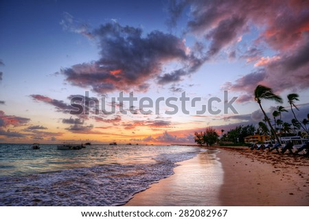 Fluffy dark clouds floating over turbulent ocean waters on sandy beach shore with palm trees at resort destination - stock photo