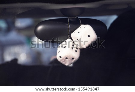 Fluffy dice hanging off the rear view mirror of a car, boy racer style. - stock photo