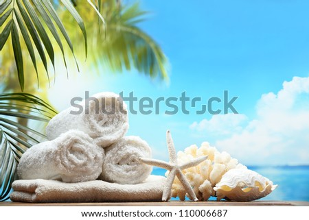 Fluffy towels and seashells on beach table - stock photo