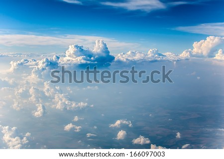 Fluffy white clouds and blue sky seen from airplane - stock photo