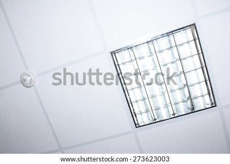 fluorescent lamp illumination and fire detector on modern office interior ceiling - stock photo