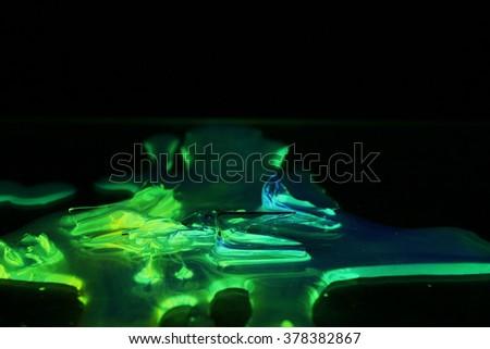 fluorescent liquid glowing in dark - stock photo
