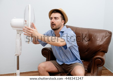 Flushed man feeling hot in front of a fan  - stock photo