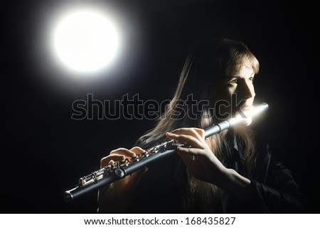 Flute music classical musician player  Flutist with musical instrument in darkness - stock photo