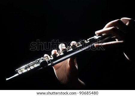 Flute music instrument details playing. Hand of flutist musician on black - stock photo