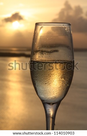 Flute of champagne with sunset background - stock photo