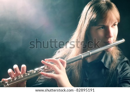 Flute playing flutist musician performer with bright musical instrument - stock photo