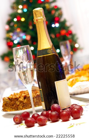 Fluted glass and champagne bottle in a Christmas celebrating table with food - stock photo