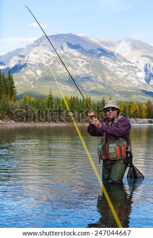 Fly fisherman Fighting a fish in a mountain river. - stock photo