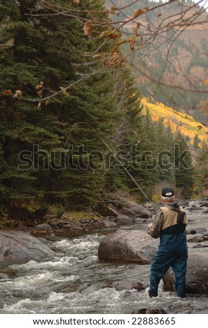 Fly Fisherman in a mountain stream with a fly rod - stock photo