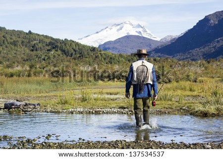 Fly fisherman walking beautiful landscape - stock photo