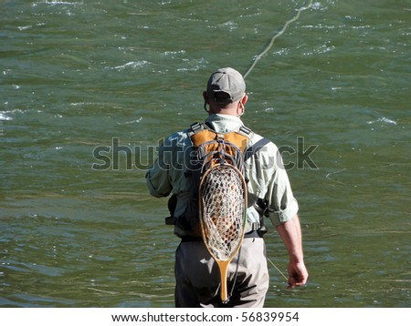 Fly fishing in a stream in the Rocky Mountains - stock photo