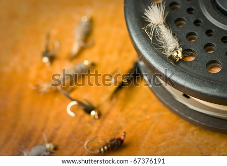fly fishing nymphs on a fly reel and antique wood. - stock photo