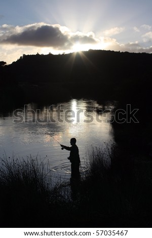 Fly fishing silhouette at sunrise - stock photo