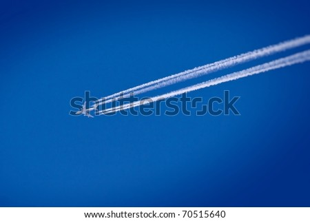 Flying airplane on the blue sky leaving white lines behind - stock photo