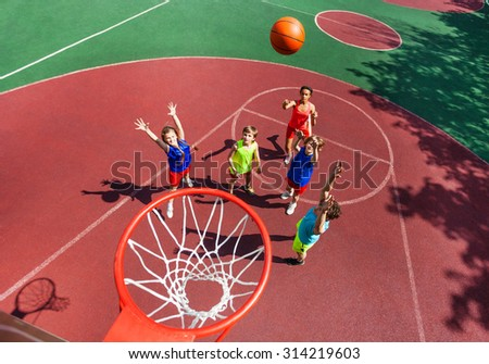 Flying ball to basket top view during basketball - stock photo
