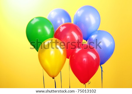 Flying balloons  on a yellow background - stock photo