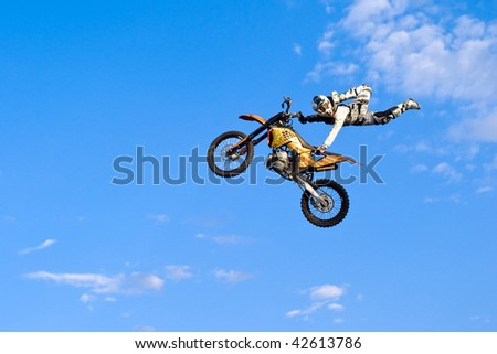 flying biker on a blue sky background - stock photo
