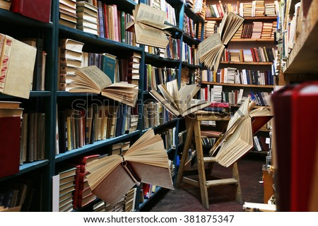 Flying books on library bookshelves background - stock photo