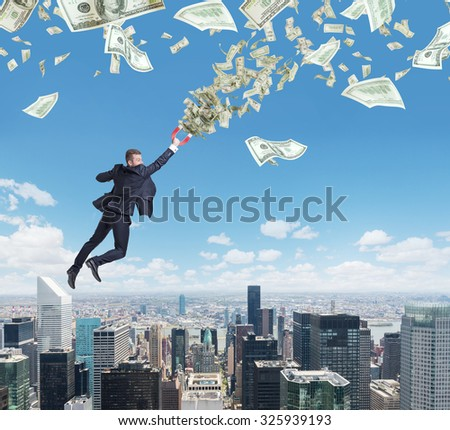 Flying confident handsome businessman with magnet attracts dollar notes. New York city on the background. - stock photo
