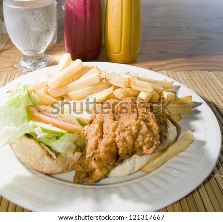flying fish sandwich Caribbean style French fries lettuce tomato photographed in St. Lawrence Gap Barbados - stock photo
