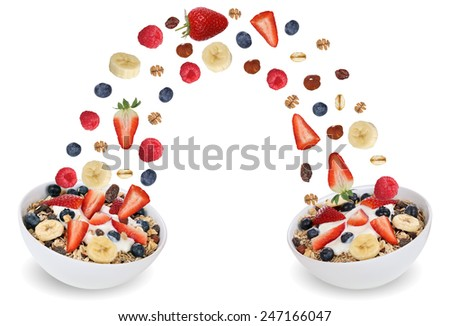 Flying fruit muesli for breakfast in bowl with fruits like raspberry, blueberries, banana and strawberry - stock photo