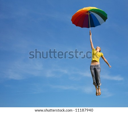 Flying girl with colorful umbrella in the blue blue sky - stock photo