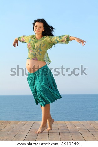 Flying happy pregnant woman on sea background - stock photo