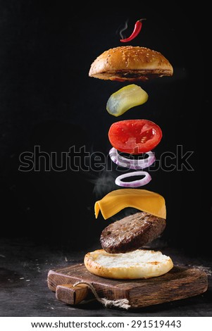 Flying ingredients for homemade burger on little wooden cutting board over dark background. - stock photo