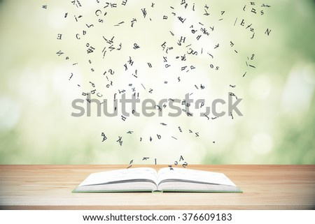 Flying letters from the opened book on wooden table - stock photo