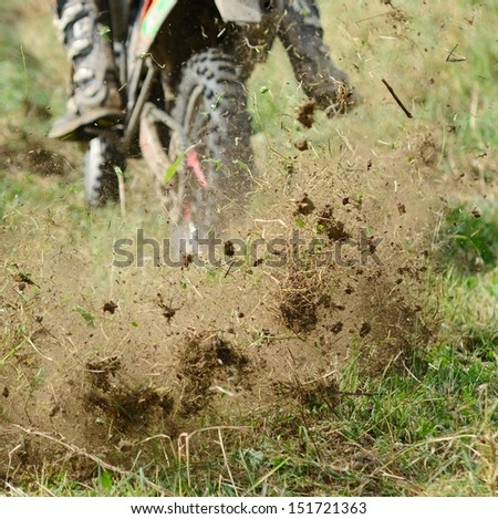 Flying mud from moving motorcycle�¢??s enduro wheel. - stock photo