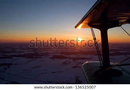 Flying on a biplane an-2  at sunset - stock photo