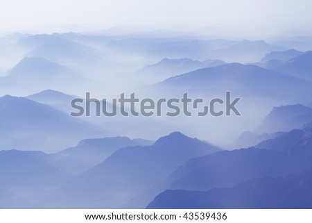 Flying over the mountains with clouds - stock photo
