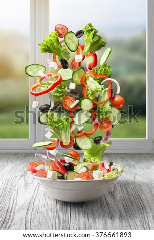 flying salad on wood against window with summer background. Greek salad: red tomatoes, pepper, cheese, lettuce, cucumber and olives - stock photo