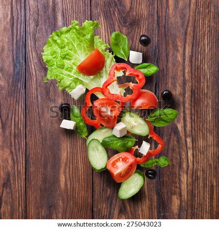 flying salad on wooden background - red tomatoes, pepper, cheese, basil, cucumber and olives - stock photo