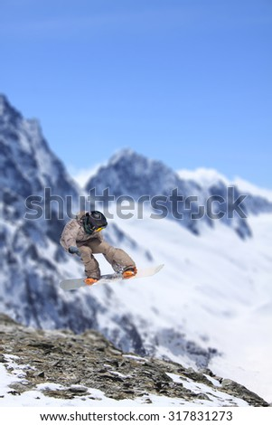 Flying snowboarder on mountains, extreme sport - stock photo