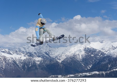 Flying snowboarder on mountains. Extreme sport. - stock photo