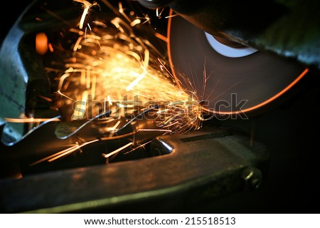 Flying sparks from a spinning grinder sharpening the teeth of an industrial saw. The edge of the grinder stone is glowing from frictional heat. - stock photo